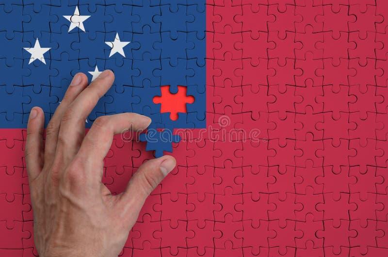 La bandera de Samoa se representa en un rompecabezas, que la mano del ` s del hombre termina para doblar fotos de archivo