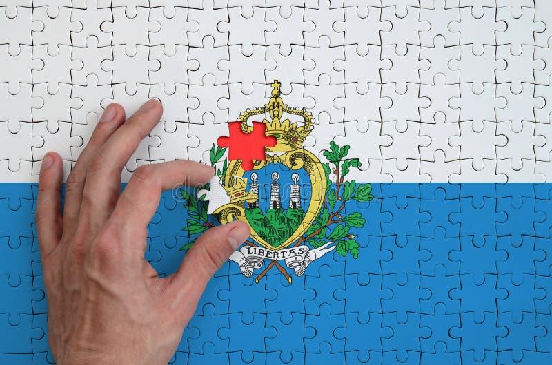 La bandera de San Marino se representa en un rompecabezas, que la mano del ` s del hombre termina para doblar imágenes de archivo libres de regalías
