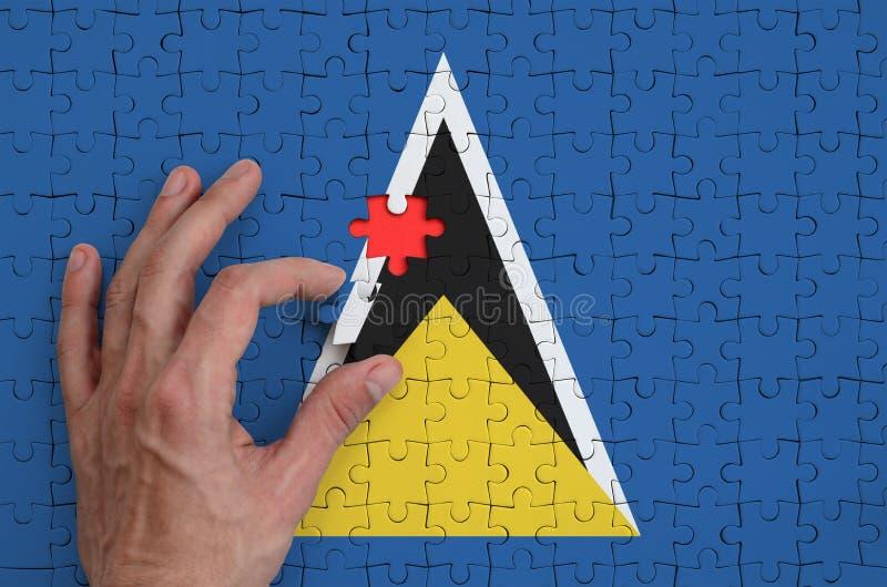 La bandera de la Santa Lucía se representa en un rompecabezas, que la mano del ` s del hombre termina para doblar fotos de archivo