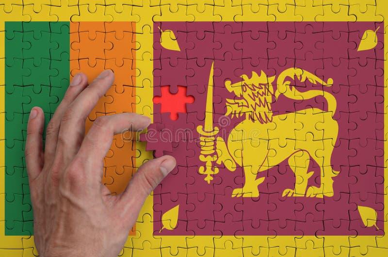 La bandera de Sri Lanka se representa en un rompecabezas, que la mano del ` s del hombre termina para doblar fotografía de archivo libre de regalías