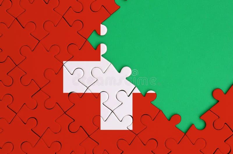La bandera de Suiza se representa en un rompecabezas terminado con el espacio verde libre de la copia en el lado derecho fotos de archivo