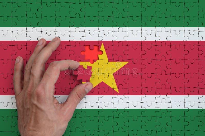 La bandera de Suriname se representa en un rompecabezas, que la mano del ` s del hombre termina para doblar imagen de archivo