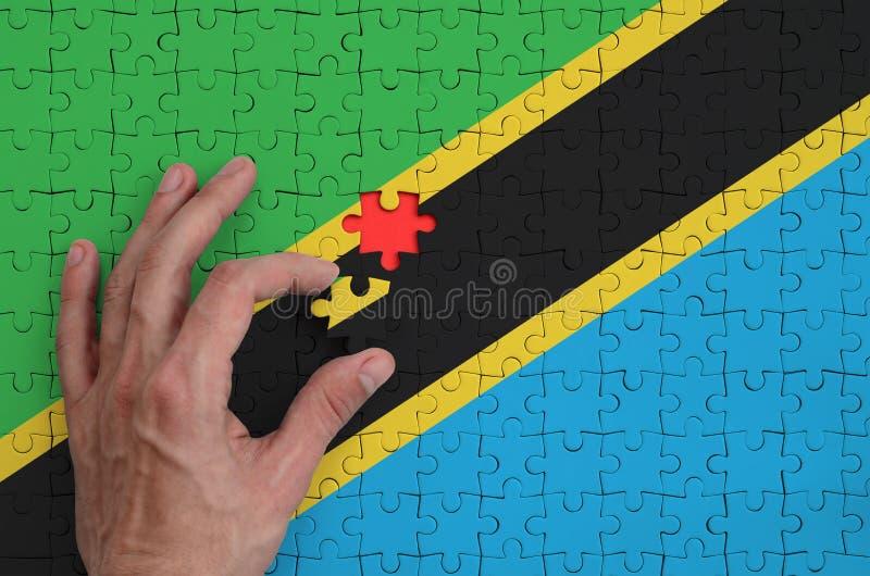 La bandera de Tanzania se representa en un rompecabezas, que la mano del ` s del hombre termina para doblar fotografía de archivo libre de regalías