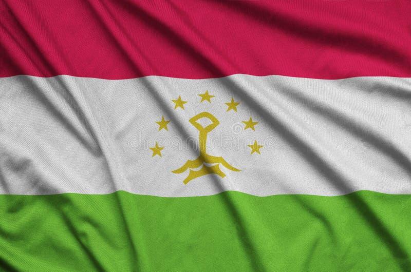 La bandera de Tayikistán se representa en una tela del paño de los deportes con muchos dobleces Bandera del equipo de deporte imagenes de archivo