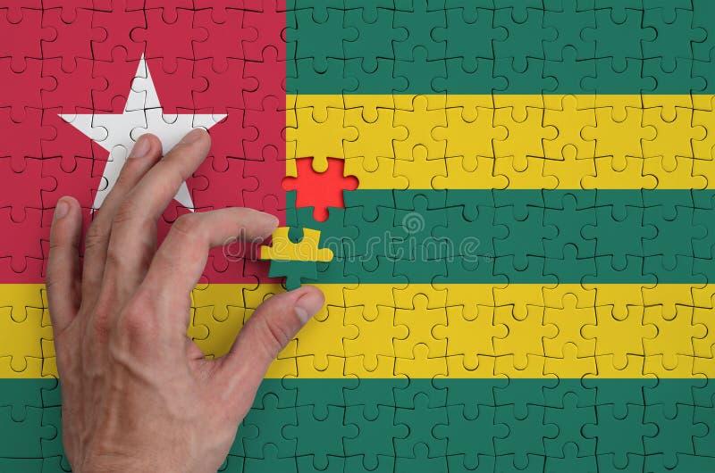 La bandera de Togo se representa en un rompecabezas, que la mano del ` s del hombre termina para doblar imágenes de archivo libres de regalías