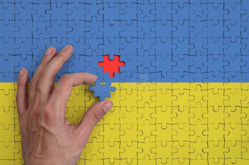 La bandera de Ucrania se representa en un rompecabezas, que la mano del ` s del hombre termina para doblar imagen de archivo libre de regalías