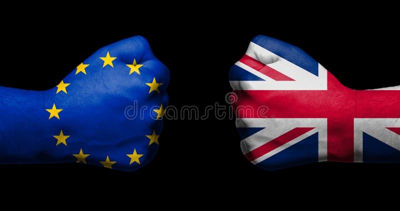La bandera de la unión europea y de Gran Bretaña pintadas en dos apretó los puños que se hacían frente en fondo/el concepto negro imagenes de archivo