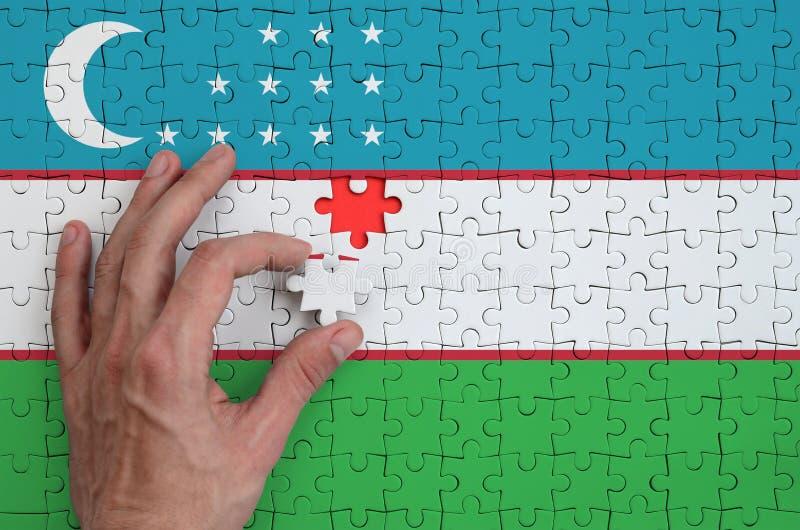 La bandera de Uzbekistán se representa en un rompecabezas, que la mano del ` s del hombre termina para doblar imagen de archivo