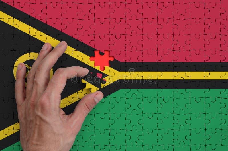 La bandera de Vanuatu se representa en un rompecabezas, que la mano del ` s del hombre termina para doblar imagen de archivo libre de regalías