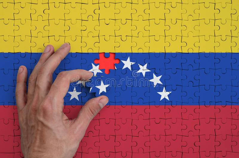 La bandera de Venezuela se representa en un rompecabezas, que la mano del ` s del hombre termina para doblar fotos de archivo