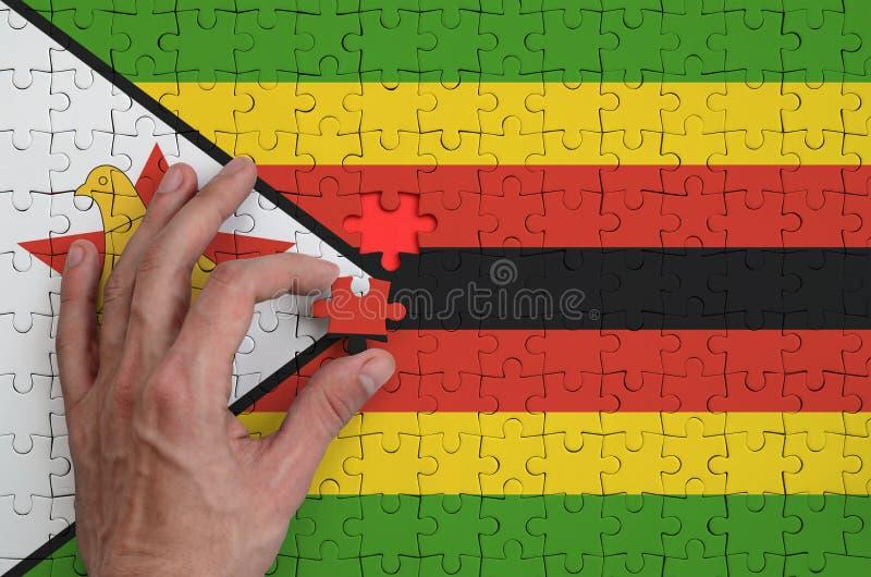 La bandera de Zimbabwe se representa en un rompecabezas, que la mano del ` s del hombre termina para doblar fotografía de archivo