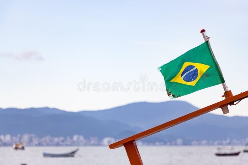 La bandera del Brasil en el top de un pequeño barco en el mar en Oporto B foto de archivo