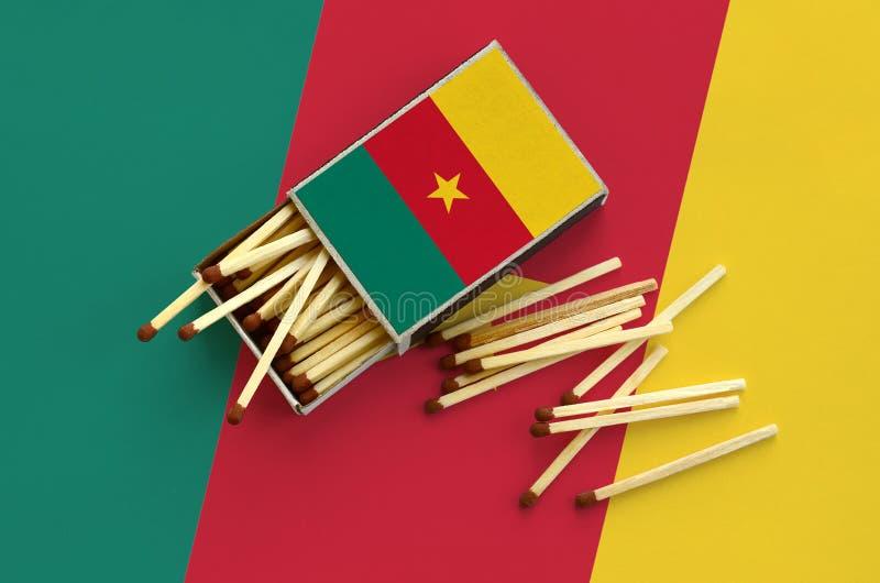La bandera del Camerún se muestra en una caja de cerillas abierta, de la cual varios partidos caen y las mentiras en una bandera  foto de archivo libre de regalías