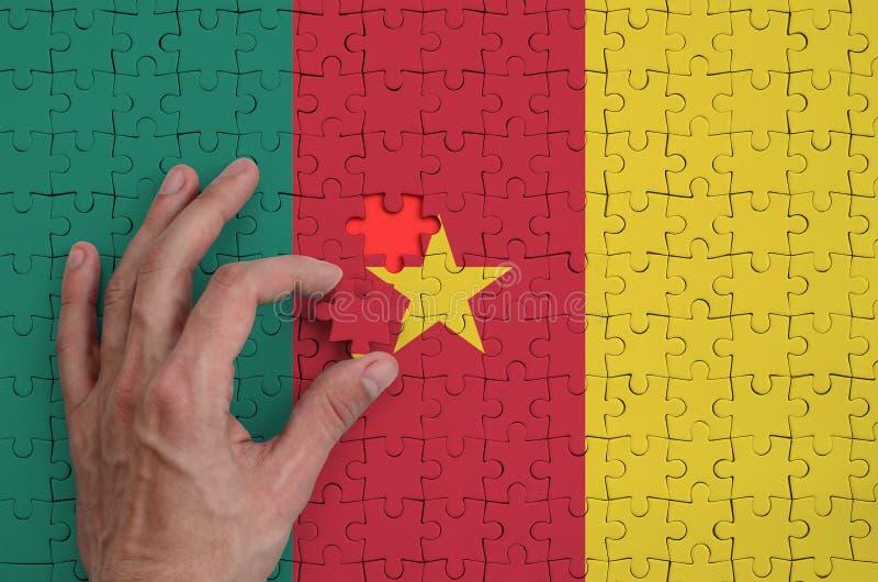 La bandera del Camerún se representa en un rompecabezas, que la mano del ` s del hombre termina para doblar foto de archivo libre de regalías