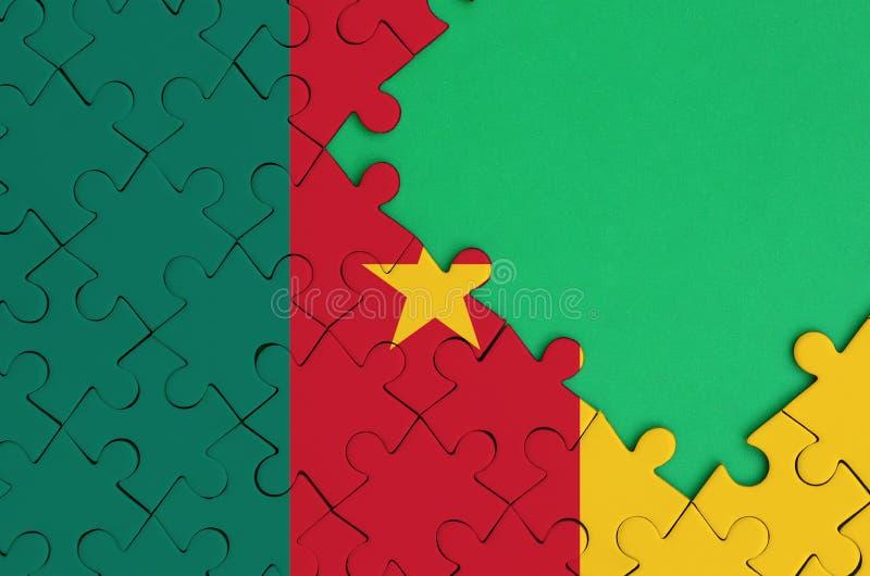 La bandera del Camerún se representa en un rompecabezas terminado con el espacio verde libre de la copia en el lado derecho fotos de archivo libres de regalías