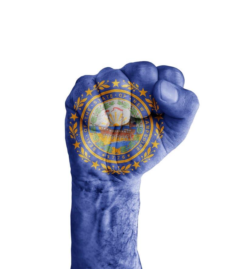 La bandera del estado de los E.E.U.U. New Hampshire pintado en el puño humano le gusta la victoria fotos de archivo libres de regalías