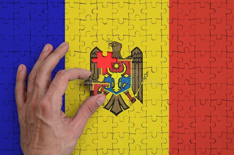 La bandera del Moldavia se representa en un rompecabezas, que la mano del ` s del hombre termina para doblar imágenes de archivo libres de regalías