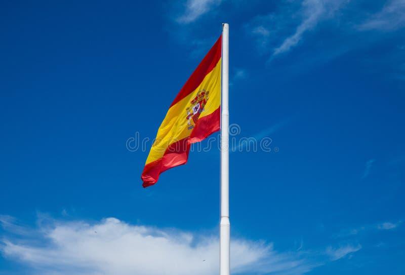 La bandera española agita contra el cielo azul en el viento imagen de archivo