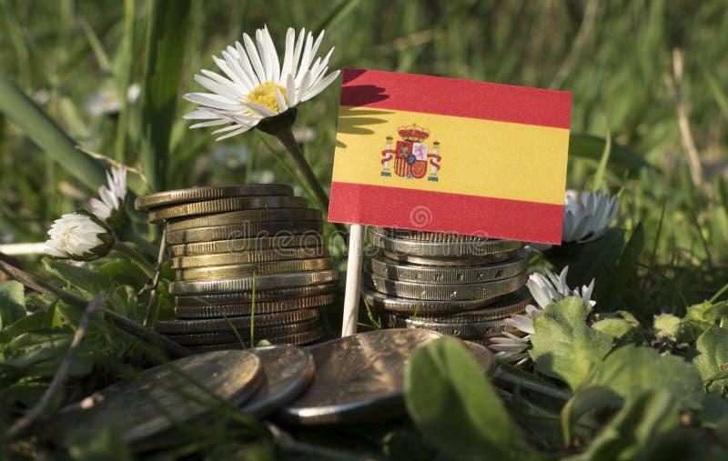 La bandera española con la pila de dinero acuña con la hierba imagen de archivo libre de regalías