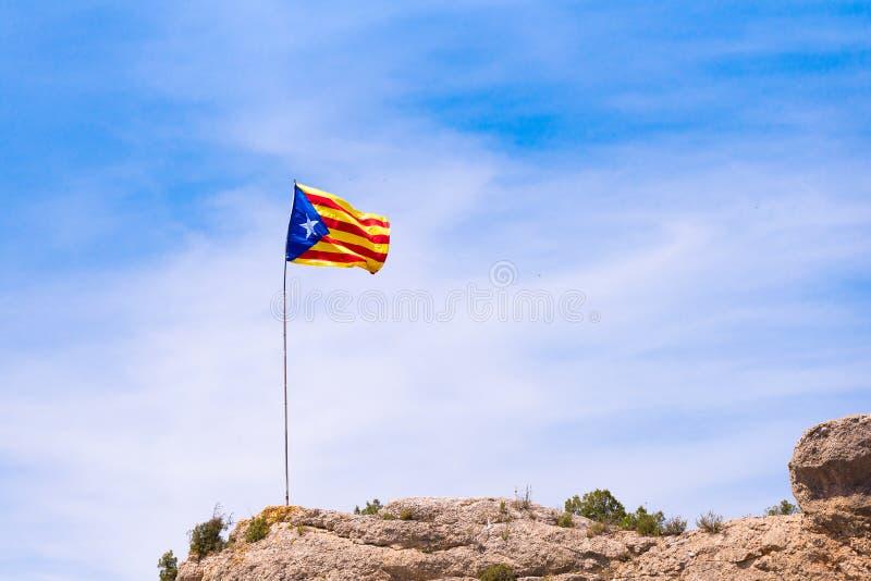 La bandera española Estelada en la montaña, sobre fondo del cielo azul, Catalunya, España Copie el espacio Espacio para el texto imagen de archivo libre de regalías