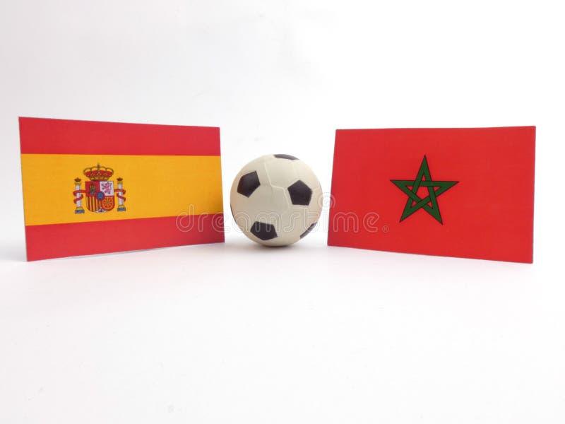 La bandera española y marroquí con la bola del fútbol isloated en blanco imágenes de archivo libres de regalías