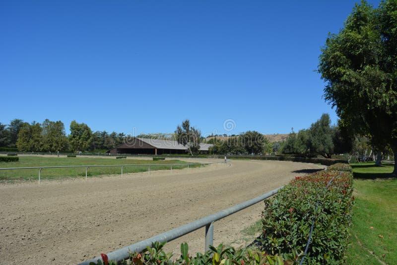 La bandera está encima de circuito de carreras de las granjas y de arena cubierta fotografía de archivo