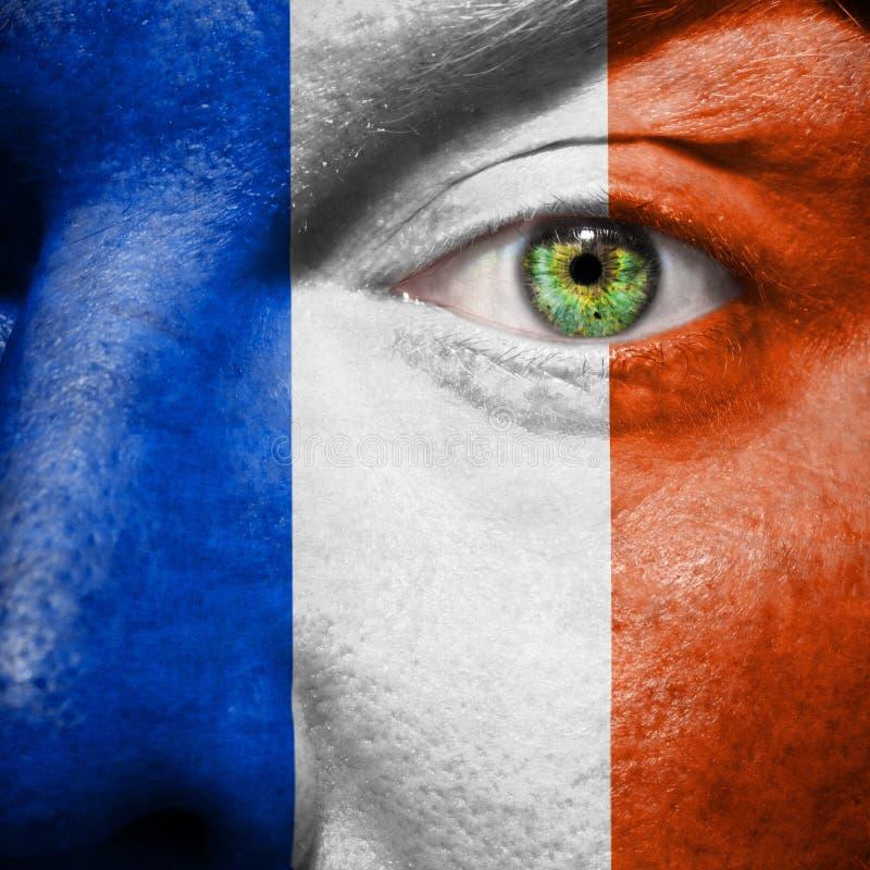 La bandera francesa pintada encendido sirve la cara foto de archivo libre de regalías