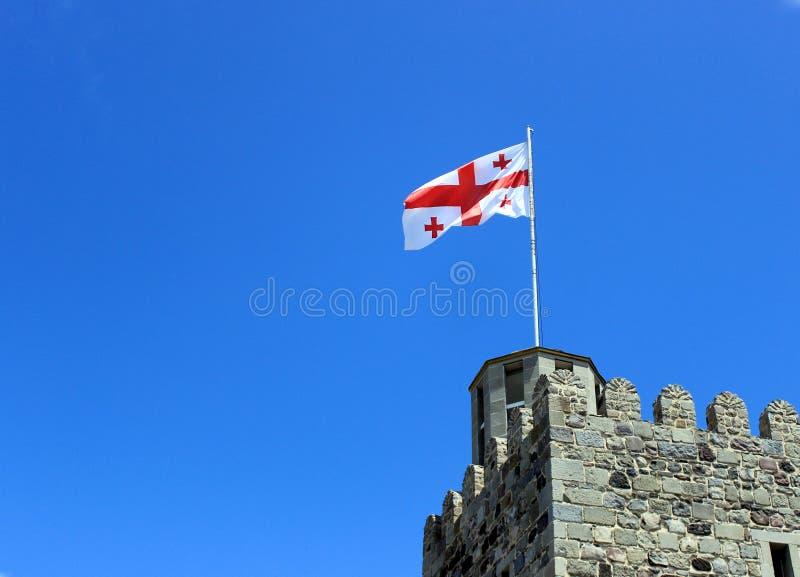 La bandera georgiana en el tejado de una torre antigua contra el cielo azul fotos de archivo
