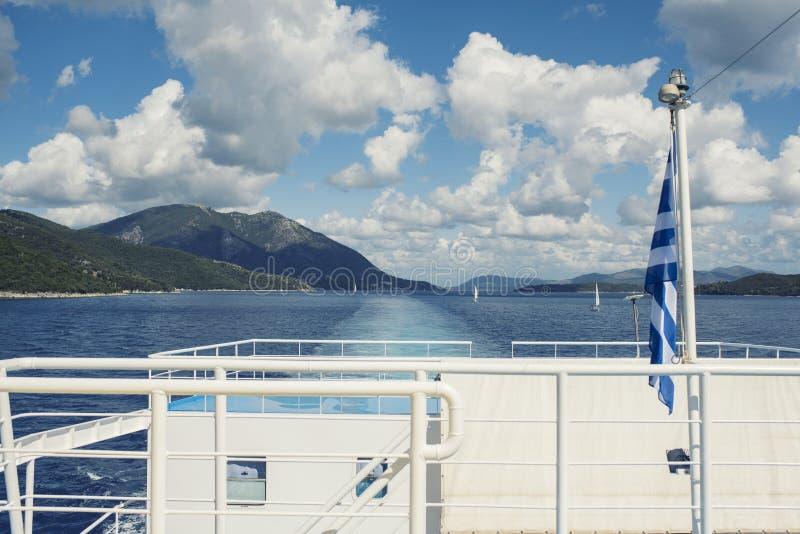 La bandera griega en la nave contra la perspectiva del mar de las islas Viaje del mar en el mar jónico