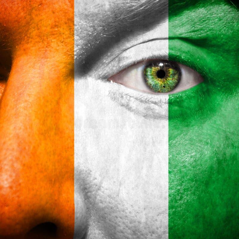 La bandera irlandesa pintada encendido sirve la cara foto de archivo