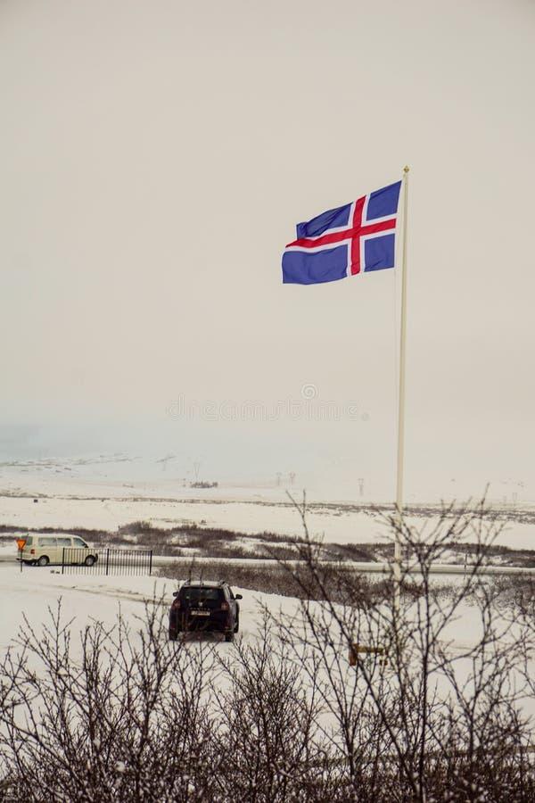 La bandera islandesa con los coches cerca de ella - imagen perfecta de la muestra para un Roadtrip a través de Islandia imagen de archivo libre de regalías