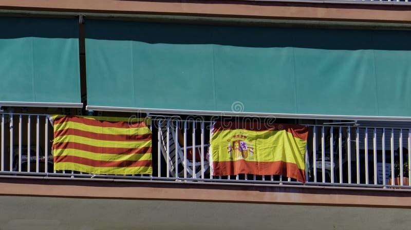 La bandera nacional de España y la bandera de Cataluña se cuelgan hacia fuera juntas en el balcón del edificio en Cataluña fotos de archivo