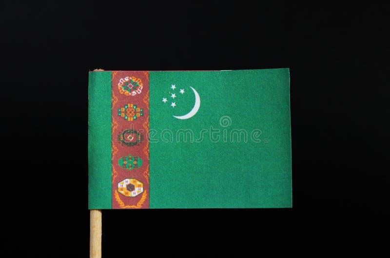 La bandera nacional de Turkmenistán en palillo en fondo negro Un campo verde con una raya roja vertical cerca del lado del alzami imagen de archivo libre de regalías