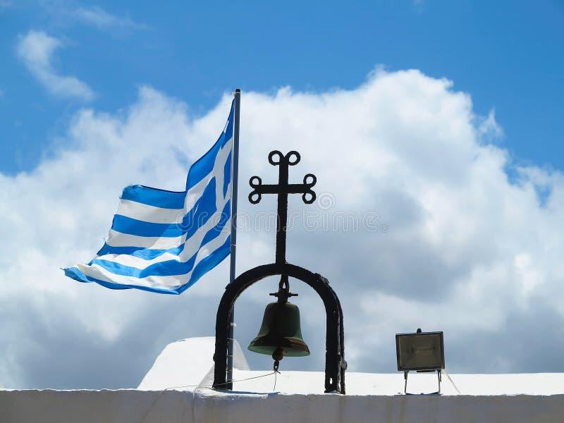 La bandera nacional griega cerca de la cruz de la pequeña iglesia contra azul foto de archivo