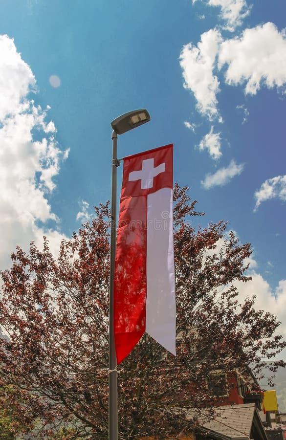 La bandera nacional suiza colgó de una lámpara de calle imágenes de archivo libres de regalías