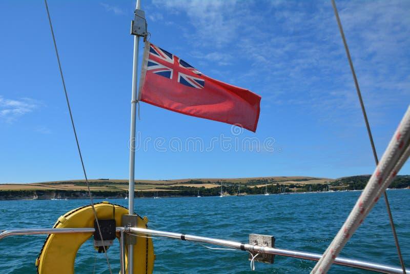 La bandera roja volada en un yate en la bahía de Studland imagen de archivo