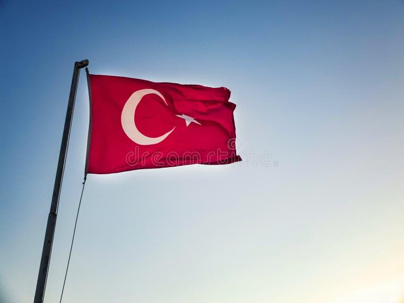 La bandera turca est? agitando contra el cielo en el fondo foto de archivo