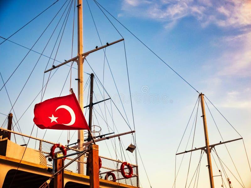 La bandera turca est? agitando en el top del buque n?utico foto de archivo