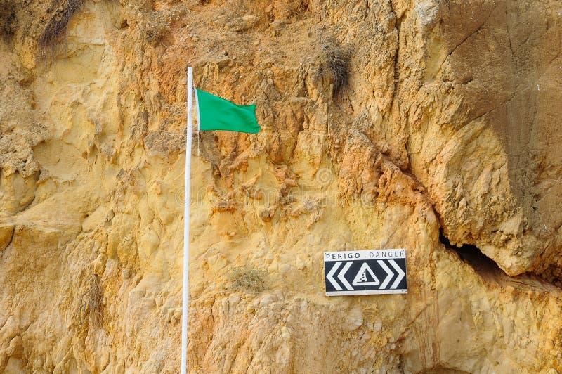 La bandera verde y el peligro firman cerca de un acantilado en una playa fotos de archivo