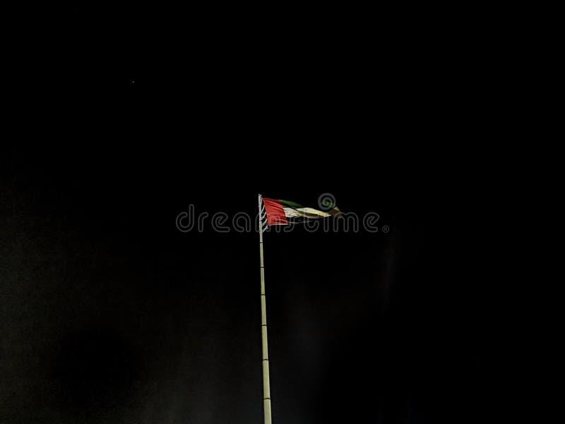 La bandiera degli Emirati Arabi Uniti che ondeggia alla notte fotografia stock libera da diritti
