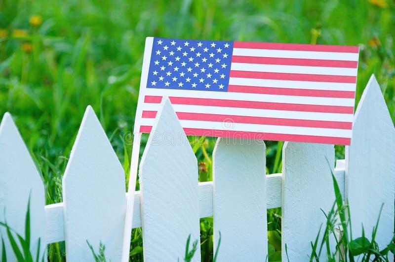 La bandiera degli Stati Uniti su un recinto bianco contro lo sfondo di erba verde di fioritura fotografia stock