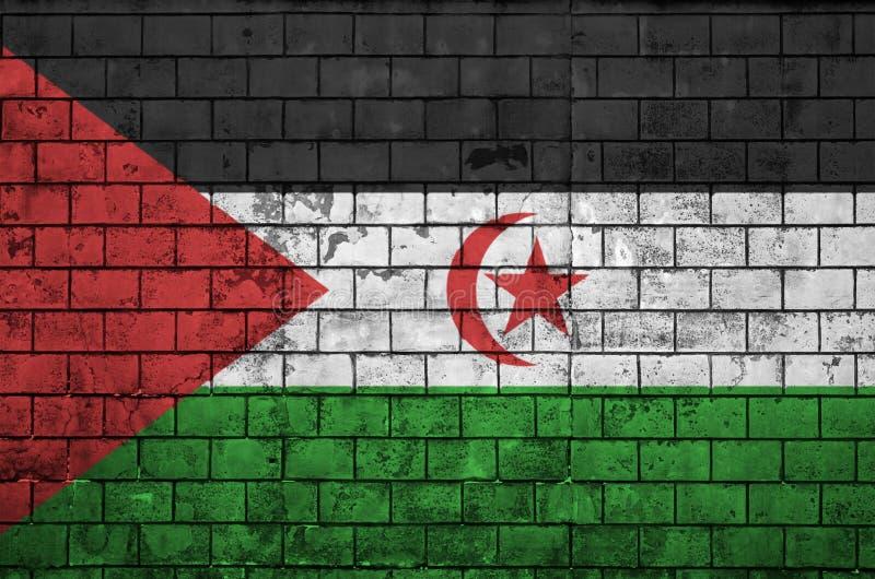 La bandiera del Sahara occidentale è dipinta su un vecchio muro di mattoni illustrazione di stock