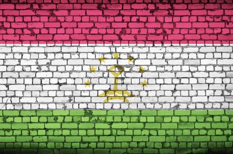 La bandiera del Tagikistan è dipinta su un vecchio muro di mattoni royalty illustrazione gratis