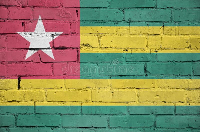 La bandiera del Togo è dipinta su un vecchio muro di mattoni fotografia stock libera da diritti