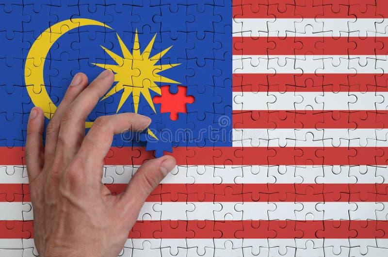 La bandiera della Malesia è descritta su un puzzle, che la mano del ` s dell'uomo completa per piegare immagine stock libera da diritti