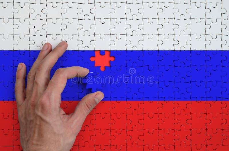 La bandiera della Russia è descritta su un puzzle, che la mano del ` s dell'uomo completa per piegare immagine stock libera da diritti