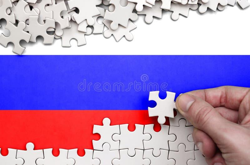 La bandiera della Russia è descritta su una tavola su cui la mano umana piega un puzzle di colore bianco fotografie stock libere da diritti