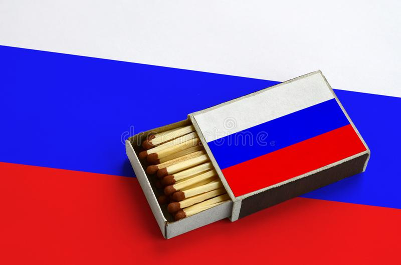 La bandiera della Russia è indicata in una scatola di fiammiferi aperta, che è riempita di partite e si trova su una grande bandi immagine stock
