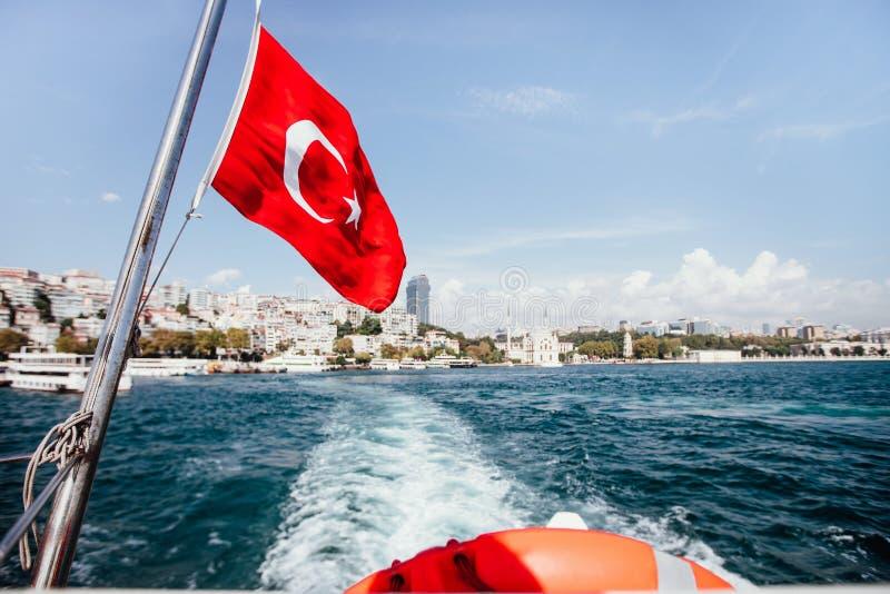 La bandiera della Turchia ed il salvagente sopra appoggiano di una barca nello stretto di Bosphorus, Costantinopoli, Turchia fotografia stock