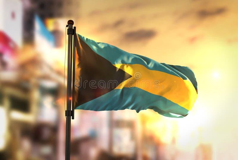 La bandiera delle Bahamas contro fondo vago città alla parte posteriore di alba fotografie stock